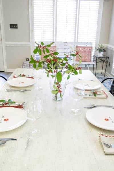 Create a festive table with live holly. This simple Christmas table setting with holly is easy and inexpensive to put together.
